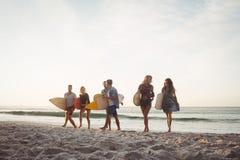 Glückliche Freunde, die mit Surfbrettern gehen lizenzfreie stockfotografie