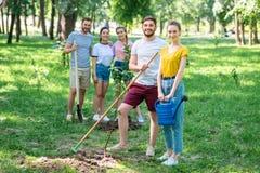 glückliche Freunde, die neue Bäume und das Freiwillig erbieten pflanzen stockfotografie