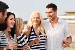 Glückliche Freunde, die nicht alkoholisches Bier auf Strand trinken stockfotografie