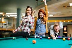 Glückliche Freunde, die Pool spielend genießen Lizenzfreies Stockfoto