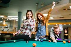 Glückliche Freunde, die Pool spielend genießen Lizenzfreies Stockbild