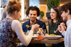 Glückliche Freunde, die am Restaurant essen stockfotografie