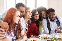Glückliche Freunde, die am Restaurant essen stockfotos