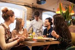 Glückliche Freunde, die am Restaurant essen und trinken stockfotos