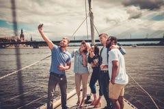 Glückliche Freunde, die selfie auf einer Yacht nehmen Lizenzfreies Stockbild