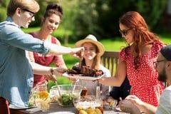 Glückliche Freunde, die am Sommergartenfest zu Abend essen lizenzfreie stockfotos
