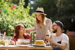 Glückliche Freunde, die am Sommergartenfest zu Abend essen lizenzfreie stockfotografie