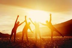 Glückliche Freunde, die Spaß gegen Sonnenuntergangberge haben lizenzfreies stockfoto