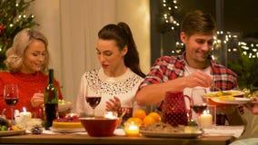 Glückliche Freunde, die Weihnachtszu Hause zu Abend essen stock footage