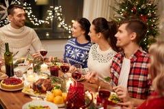 Glückliche Freunde, die Weihnachtszu Hause zu Abend essen stockfotos