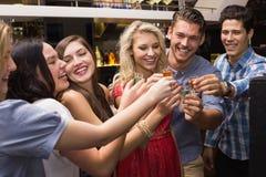 Glückliche Freunde, die zusammen etwas trinken Lizenzfreie Stockfotos