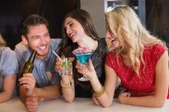 Glückliche Freunde, die zusammen etwas trinken Lizenzfreie Stockfotografie