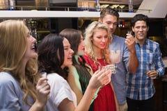 Glückliche Freunde, die zusammen etwas trinken Stockbild