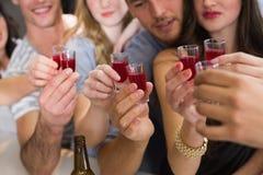 Glückliche Freunde, die zusammen etwas trinken Stockbilder