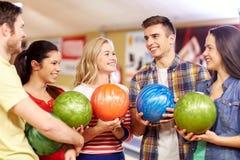 Glückliche Freunde im Bowlingspielverein lizenzfreies stockfoto