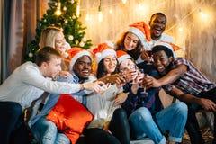 Glückliche Freunde mit Champagner Weihnachten feiernd stockbild