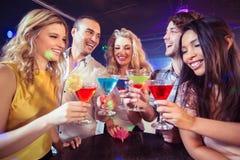 Glückliche Freunde mit Cocktails Stockfotografie