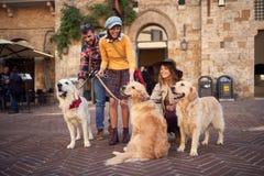 Glückliche Freunde mit dem Hund, der im Urlaub Spaß lacht und hat stockfoto
