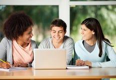Glückliche Freunde mit dem Laptop, der im Klassenzimmer sitzt Stockfoto