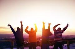 Glückliche Freunde mit den angehobenen Händen bei Sonnenuntergang stockbilder