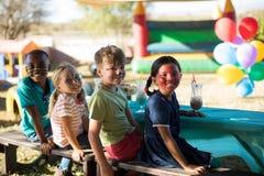 Glückliche Freunde mit der Gesichtsfarbe, die Getränke beim Sitzen auf Bank am Park hat Stockbild