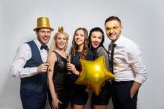 Glückliche Freunde mit der goldenen Parteistützenaufstellung stockfotos
