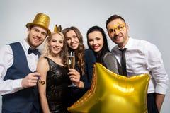 Glückliche Freunde mit der goldenen Parteistützenaufstellung stockfotografie
