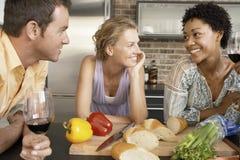Glückliche Freunde mit der Zubereitung des Lebensmittels an der Küchenarbeitsplatte Stockbilder