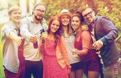 Glückliche Freunde mit Getränken am Sommergartenfest lizenzfreies stockfoto