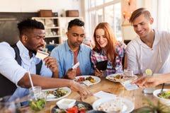 Glückliche Freunde mit Lohnliste des Geldes am Restaurant Stockfotografie