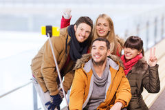Glückliche Freunde mit Smartphone auf Eisbahn Stockbild
