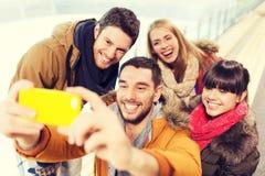 Glückliche Freunde mit Smartphone auf Eisbahn lizenzfreies stockbild