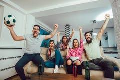 Glückliche Freunde oder Fußballfane, die Fußball im Fernsehen aufpassen stockfotografie
