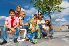 Glückliche Freunde sitzen auf Stühlen des Dammes Stockbilder