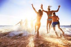 Glückliche Freunde am Sonnenuntergangseestrand lizenzfreies stockfoto