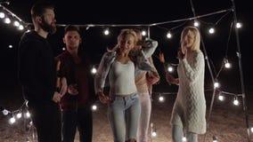 Glückliche Freunde tanzt zusammen am Sand auf Nachtstrand auf Hintergrund des Dekors mit Lampen stock footage