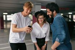Glückliche Freunde unter Verwendung des Handys am Parkplatz lizenzfreie stockbilder
