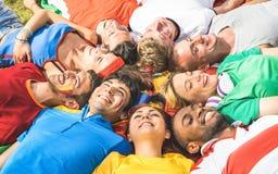Glückliche Freundgruppe, die auf Wiese nach Weltfußballereignis - Franc liegt stockfotografie