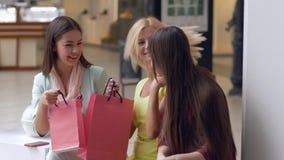 Glückliche Freundinnen besprechen Neuanschaffungen in den Paketen von den teuren Butiken, die von den Verkäufen und von den Rabat stock footage