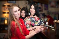 Glückliche Freundinnen, die an der Bar mit Cocktails sitzen Stockfotos