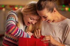 Glückliche Freundinnen, die in der Einkaufstasche schauen Stockbilder