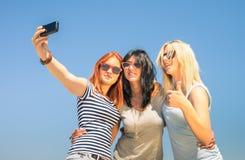 Glückliche Freundinnen, die selfie gegen blauen Himmel nehmen Lizenzfreies Stockfoto