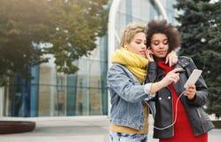 Glückliche Freundinnen hören Musik draußen Lizenzfreies Stockbild