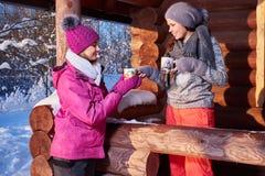 Glückliche Freundinnen verbringen Winterurlaube am Gebirgshäuschen Stockfotografie