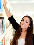 Glückliche freundliche junge Frau, die für ein Buch erreicht lizenzfreie stockbilder