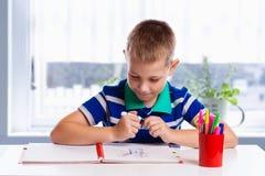 Glückliche freundliche Kindzeichnung mit Pinsel im Album unter Verwendung vieler Anstrichhilfsmittel Hand, die lego Wand aufbaut Stockfotografie