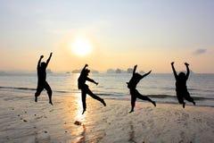 Glückliche Freundschaft, die am Strand springt stockfoto