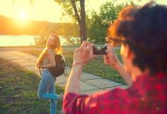 Glückliche frohe junge Paare, die Foto auf Smartphone im Sommerpark machen stockfotos