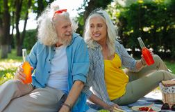 Glückliche frohe Paare, die ein Picknick haben stockfotografie