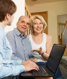 Glückliche gealterte Paare, die mit Angestelltem mit Laptop sprechen Stockfoto